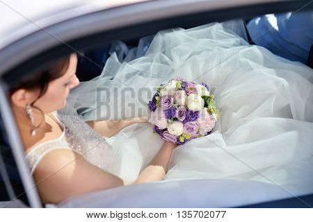 Beauty Bride In Bridal Gown With Bouquet And Lace Veil In The Car. Beautiful Model Girl In A White W