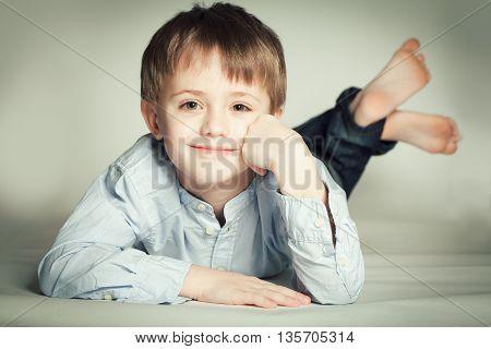 Smiling little boy lying on the floor