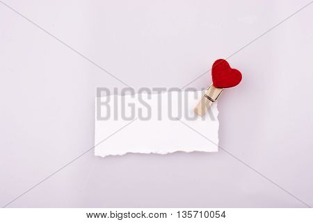 Red hearted clip on an empty torn paper