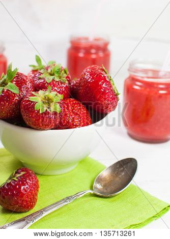 Fresh strawberries in a white bowl. On a white wooden surface.