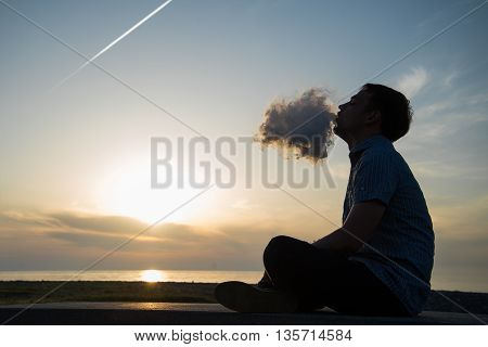 Silhouette of man smoking a pipe in cap at sunset. Photographer in a baseball cap smoking a pipe at sunset by the sea.Travel, adventure, meditation, relaxation, vacation