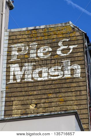 An old-fashioned painted sign for a Pie and Mash shop in England.
