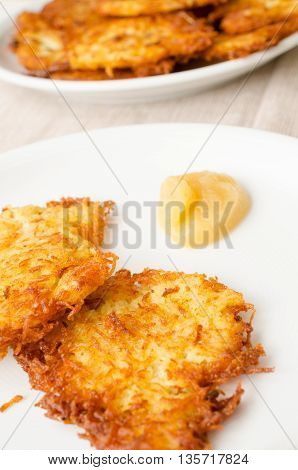 Potato fritters and applesauce on a white plate in a restaurant