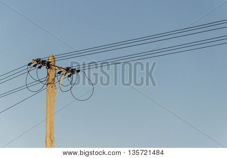 view of the head of an old-fashioned electric pole with wires and cables
