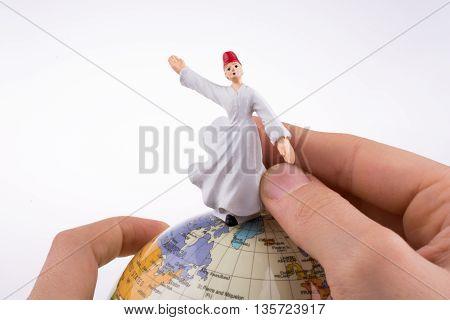 Hand holding a Sufi Derviş on a globe