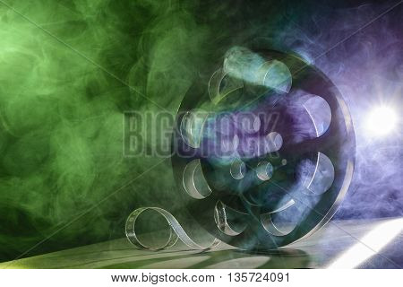 Metal reel of film is in the smoke at the table