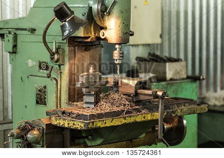 Drilling machine in operation revolves the spindle the machine studded with steel shavings. A few finished parts in the frame