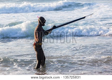 Diver loads spear gun line buoy beach ocean swimming entry.