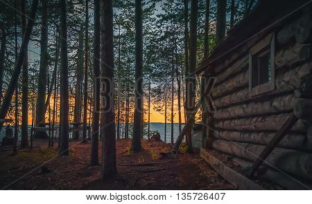 Old fishing hut in the woods on the shore of Lake Onega at sunset.