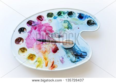 Watercolor palette with blobs of paint and brush