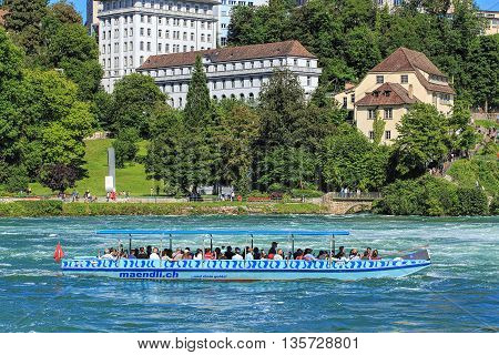 Neuhausen am Rheinfall, Switzerland - 22 June, 2016: people in a boat on the the Rhine river just below the Rhine Falls. The Rhine is a European river that begins in the Swiss canton of Graubuenden in the southeastern Swiss Alps.