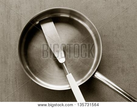 used clean empty stainless steel frying pan and spatula overhead view on the gray background black white photos. closeup top view