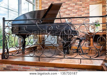 Fragment of the interior with forged fence and piano