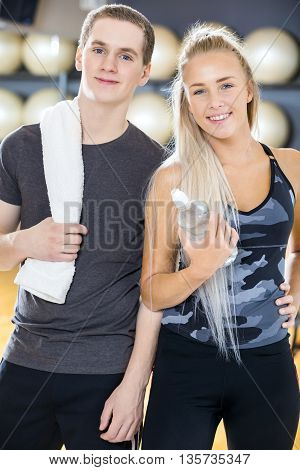 Smiling young woman and man taking a break from training at the fitness gym. Team resting after workout.