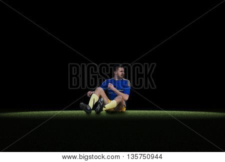 Caucasian young soccer player sitting on green grass isolated