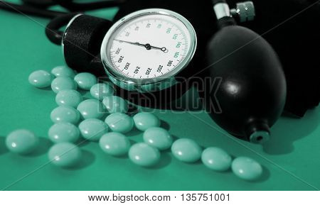 medical set for measuring blood pressure and tablets isolated on green background