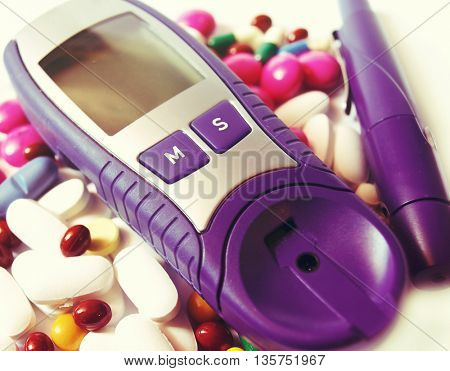 device for measuring blood sugar level isolated on white background and pills