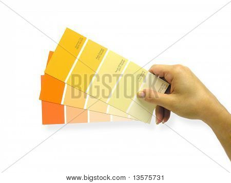A photo of a woman holding paint swatches to a wall