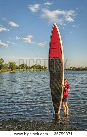 male paddler with his long stand up paddleboard on a lake shore