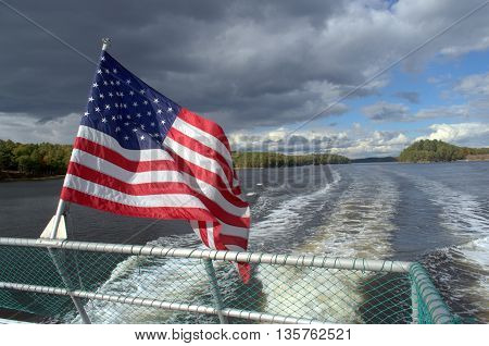 Waving American Flag on a boat with exhaust trailing behind.  Dramatic clouds in sky.