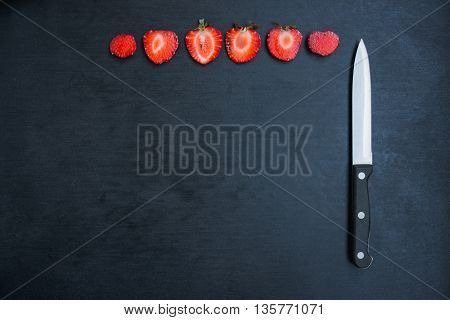sliced strawberries and knife on black background with copyspace