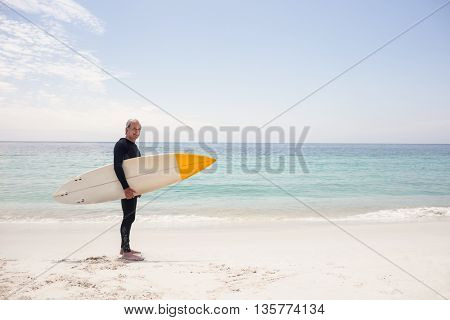 Portrait of senior man in wetsuit holding a surfboard on the beach