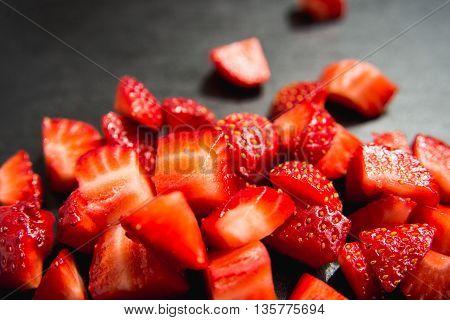 lobule sliced strawberries on black slate background