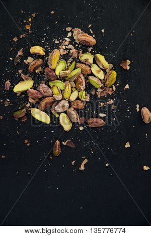 pile of pistachios on a black slate surface