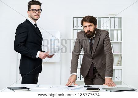 Two handsome businessmen standing at office deak with various items and looking at the camera