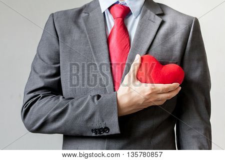 Businessman Showing Compassion Holding Red Heart Onto His Chest In His Suit - Crm, Service Mind Busi