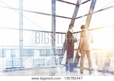 Two businessmen discussing contract in interior with New York city view and sunlight. Double exposure