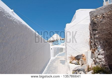 Narrow whitewashed street in Fira town on the Santorini (Thira) island in Greece.
