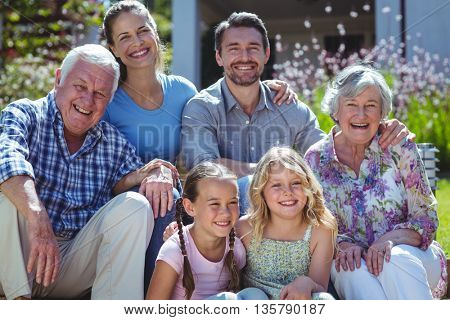 Portrait of cheerful family sitting in back yard