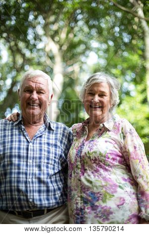 Portrait of happy couple standing against trees in back yard