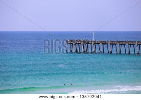 PENSACOLA BEACH, USA - MAY 13, 2015: Looking from the beach towards Pensacola Beach Gulf Pier. There are people fishing on the pier and also some swimming in the water.