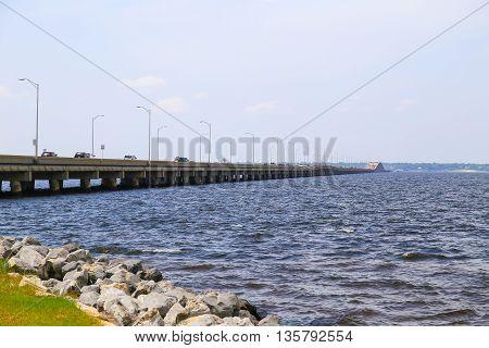 PENSACOLA BEACH, USA - MAY 13, 2015: View of the Pensacola Beach Bridge crossing the Santa Rosa Sound towards Gulf Breeze with plenty of cars driving on the bridge.