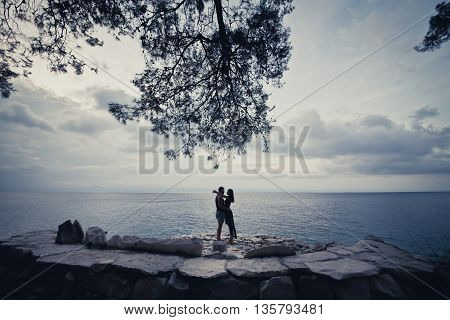 Loving couple share a romantic moment on sea side with wonderful sea view. Couple kissing after romantic engagement proposal. Young couple in love enjoying romantic evening.Date.Honeymoon poster