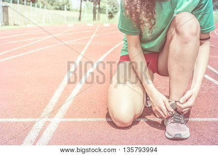 young female athlete on running track tying shoes ready to run during preparations for championship competition