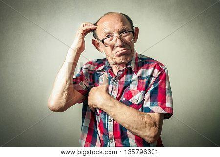 portrait of the funny senior man thinking