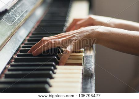 Woman playing old rusty piano, selective focus, hands on keyboard detail, blurred background