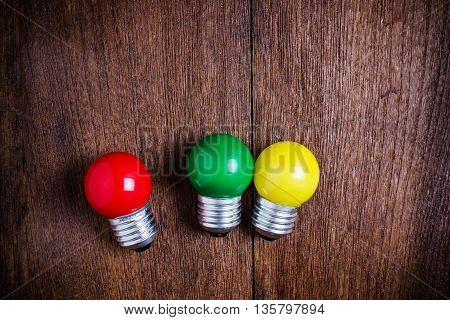 top view redgreenyellow light bulbs on wooden background.