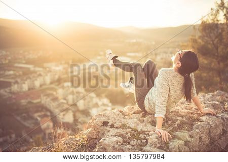Carefree happy woman sitting on top of mountain edge cliff enjoying sun on her face. Enjoying nature sunset. Resting form daily problems. Freedom.Enjoyment.Relaxing in mountains at sunrise.Daydreaming Carefree happy woman sitting on top of mountain edge c