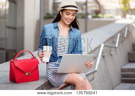 Express yourself. Cheerful delighted smiling woman sitting on the handrail and using laptop while drinking coffee