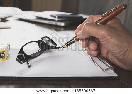 Hand Holding Pen With Notepad And Eyeglasses On Office Desk