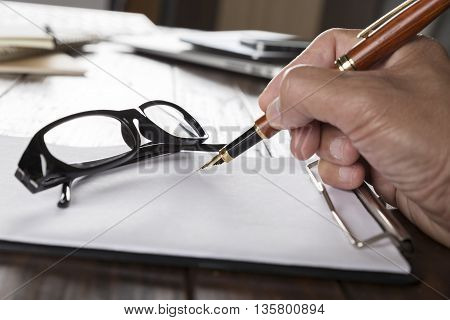 hand holding pen with notepad and eyeglasses on wooden office desk