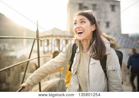 Excited woman looking surprised and amazed,speechless with mouth open.Young tourist backpacker woman excited,overwhelmed,looking at something amazing on her trip.Traveling on beautiful places