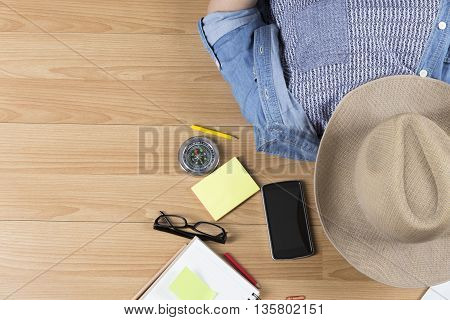 Woman Lying On Floor With Hat, Mobile Phone, Notebook And Map