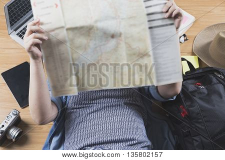 Woman Lying On Floor With Map, Backpack And Camera