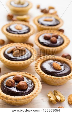 Nutty chocolate dessert small tarts on a white background.