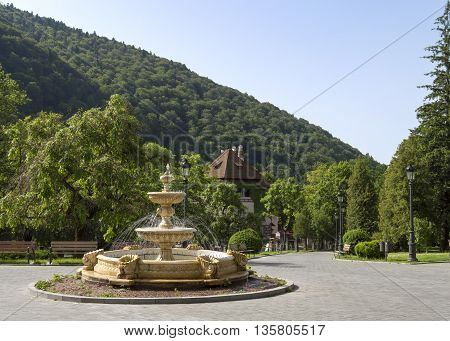 Sinaia, ROMANIA - June 18 2016: The fountain located in front of Sinaia Casino with a view towards the city. SINAIA - June 18 2016